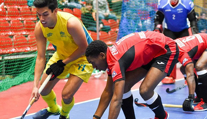 Trinidad and Tobago's Kristien Emmanuel (centre) tries to get the ball from Australia's Jake Sherren (left) during yesterday's match in the FIH Indoor Hockey World Cup in Berlin, Germany. Also in photo are TT's captain Solomon Eccles (right) and goalkeeper Ron Alexander. PHOTO COURTESY FIH.