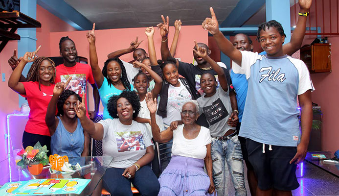 Relatives and friends of Jereem Richards, including his mother Yvette Wilson (seated center) and grandmother Deaprice Wilson (seated right) celebrate his victory at the family's home in Point Fortin yesterday.