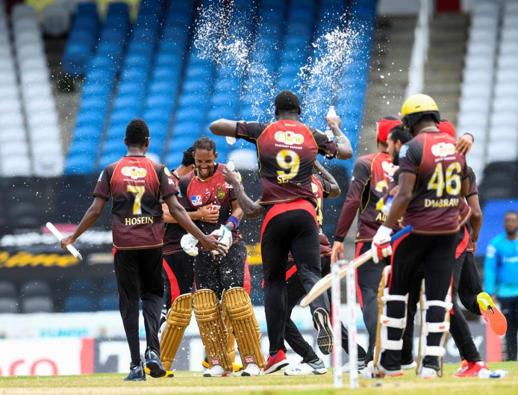 Lendl Simmons (2L) and Trinbago Knight Riders team-mates celebrate winning the Hero Caribbean Premier League 2020, at Brian Lara Cricket Academy,Tarouba, on Thursday. - CPL T20 via Getty Images
